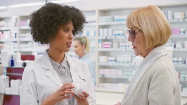 female salesperson at the drugstore advising a senior woman about a mineral supplement - lekarstwo filmów i materiałów b-roll