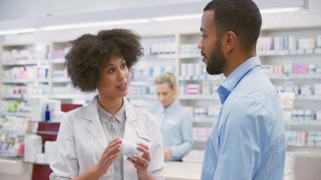 Female salesperson at the drugstore advising a young man about a vitamin supplement