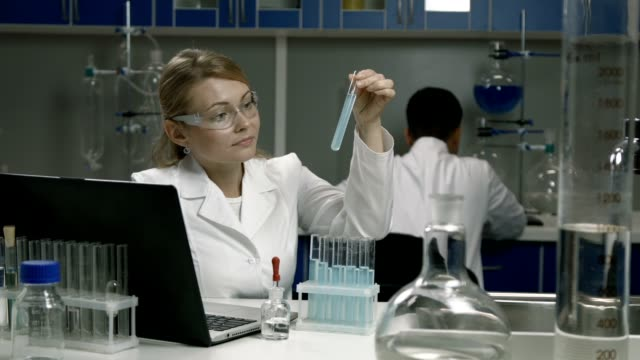 Female scientist conducting an experiment in lab video