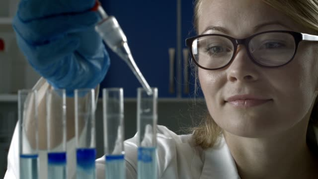 Female scientist dropping liquid into test tubes video