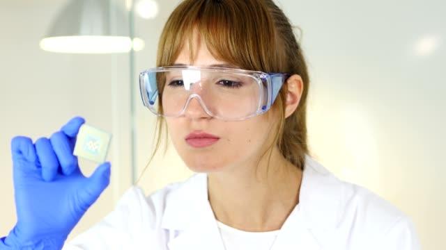 コンピューターの新しいチップを調べる女性科学者 - 半導体点の映像素材/bロール