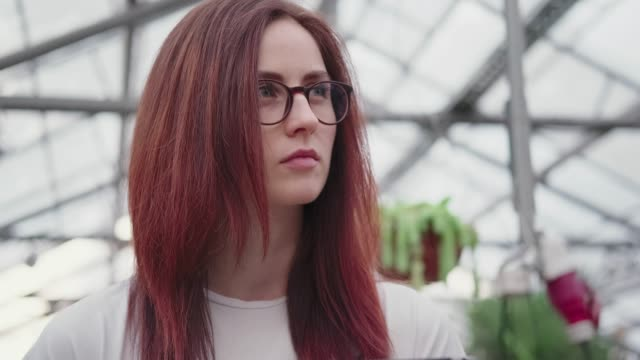 female scientist in a greenhouse on the background of the glass roof - giardino botanico video stock e b–roll