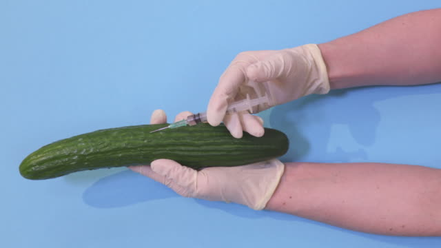 Female scientist injecting green cucumber.GMO food concept - vídeo