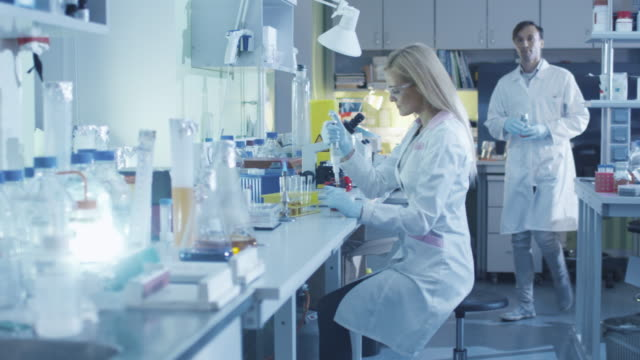 Female scientist is using a micro pipette while working in a laboratory with colleagues. video