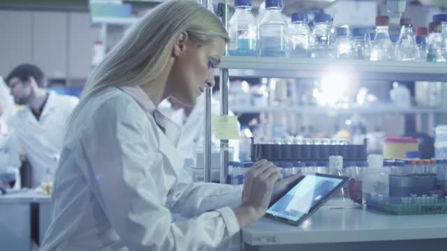 weibliche wissenschaftlerin benutzt eine tablette, während sie im labor arbeitet. - medizinexamen stock-videos und b-roll-filmmaterial