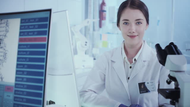 Female scientist satisfied with her work. Futuristic Genetic Research Laboratory Female Scientist studying human DNA. Protective workwear biosensor stock videos & royalty-free footage