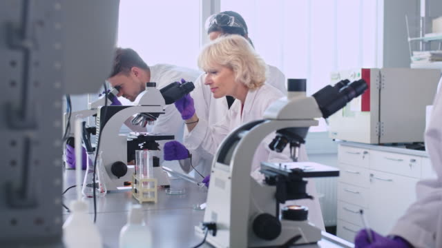 female scientist using microscope in laboratory - dokładność filmów i materiałów b-roll