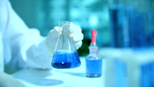 wissenschaftlerin arbeitet mit becher - wissenschaftlerin stock-videos und b-roll-filmmaterial