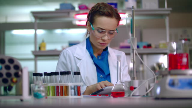 female scientist working with scientist tablet. woman scientist using tablet pc - science research stock videos & royalty-free footage