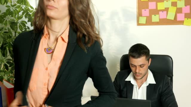 Female secretary standing in front of her boss's desk video