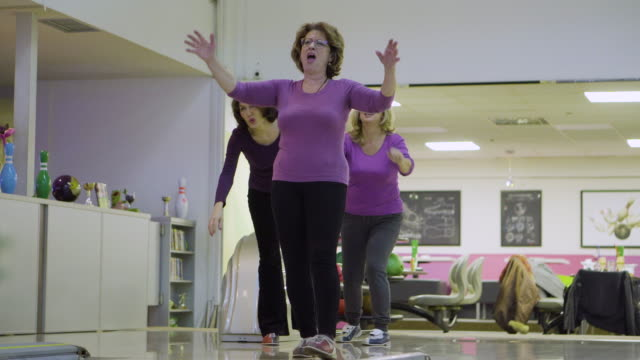 Female senior friends having fun in bowling alley video