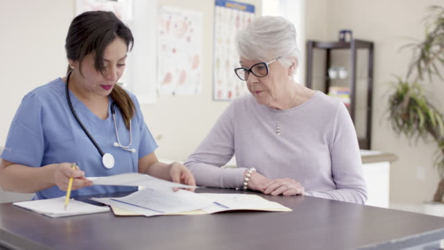 Female Senior Patient With Ethnic Nurse In Appointment A senior caucasian woman talks to her ethnic nurse about how she is currently feeling. They are engaged with one another and discussing treatment plans together. explaining stock videos & royalty-free footage