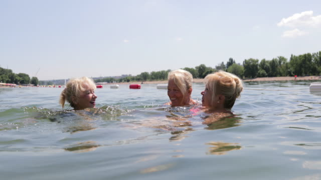 Female seniors swimming, handheld shot video