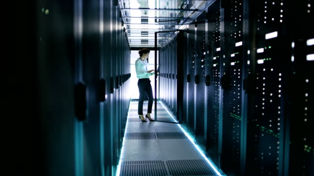 Female Server Engineer In Data Center Works on Rack Server with Her Laptop. video