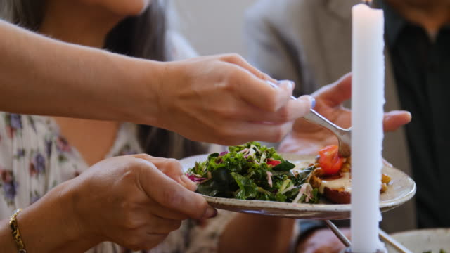 Female serving tomatoes in plate to woman at party