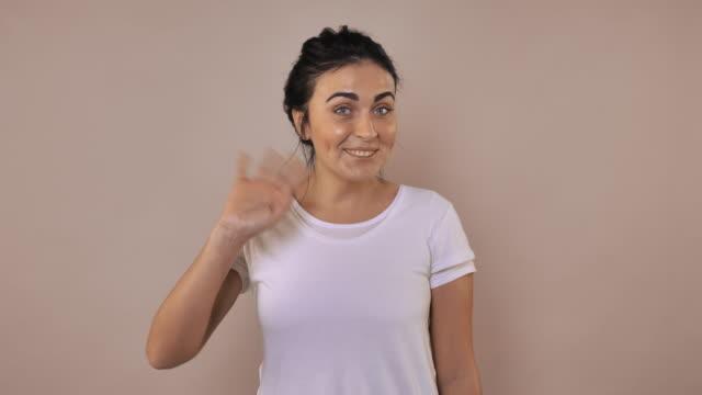 female shows sign hi - maglietta bianca video stock e b–roll