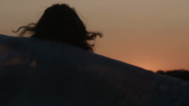 Female silhouette enjoying view of pink sky at sunset, holding video