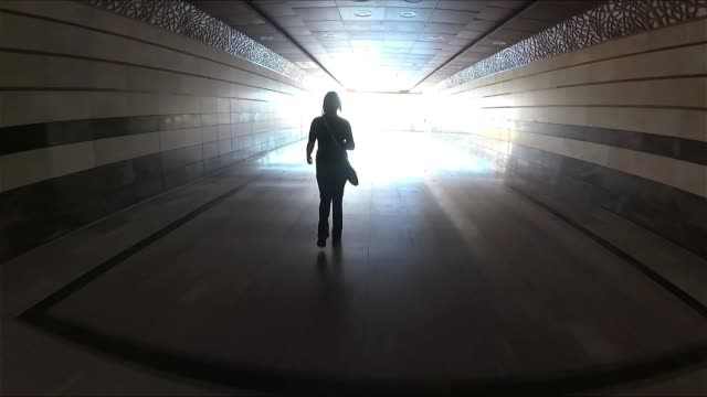 光の背景に対する地下道の女性シルエット - 方向点の映像素材/bロール