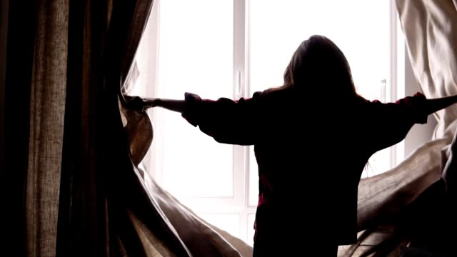 Female silhouette opens up the beige curtains and lets the ligh go into the room. video