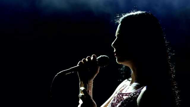 female singer on the stage holding a microphone. - cantante video stock e b–roll