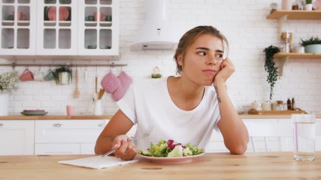 テーブルに座っている女性は、サラダを食べたくないダイエットに不満を感じています。モダンなキッチンインテリア。健康的な栄養、摂食障害。クローズアップ - 体への関心点の映像素材/bロール