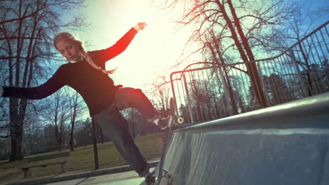 slo mo kvinnlig skateboardåkare hoppar upp i luften i solsken - skatepark bildbanksvideor och videomaterial från bakom kulisserna