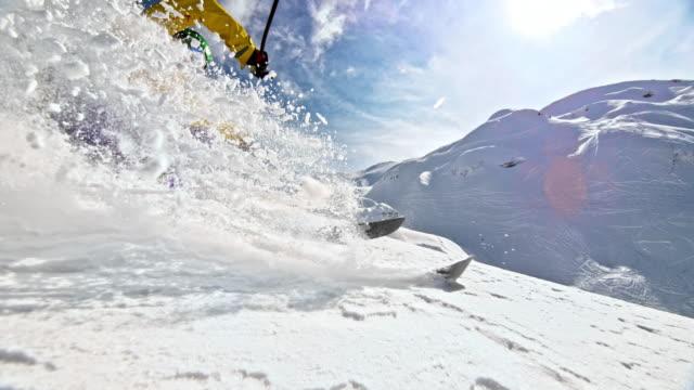 slo mo female skiing in powder snow splashing the camera - sci sci e snowboard video stock e b–roll