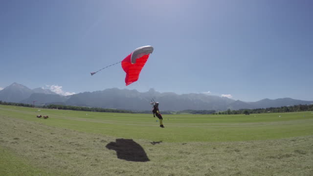 female skydiver comes in for landing on open field - base jumping video stock e b–roll