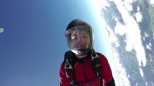 female skydiver in freefall above clouds and distant horizon - base jumping video stock e b–roll