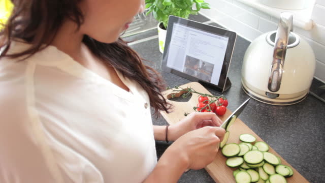 Female slicing vegetables in kitchen looking at ipad video