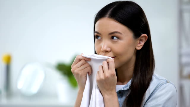 Female smelling fresh linens and smiling, enjoying fabric conditioner aroma