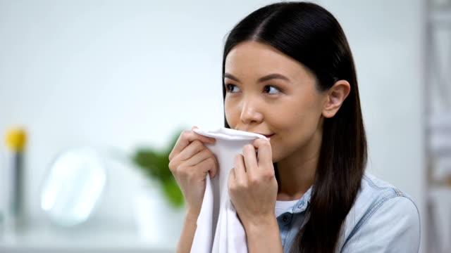 vídeos de stock, filmes e b-roll de linhos e sorriso frescos de cheiro fêmeas, apreciando o aroma do condicionador da tela - vestuário