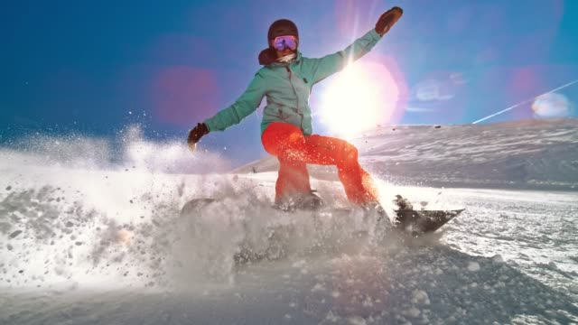 speed ramp female snowboarder causing a powder splash in sunshine - snowboarding video stock e b–roll