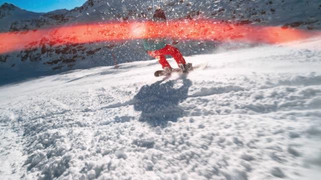 速度ランプ ts の女性スノーボーダーはフレアで太陽の下で雪を覆う山を下降させる - スポーツ用品点の映像素材/bロール
