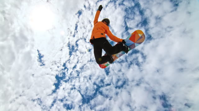speed ramp female snowboarder grabbing her snowboard while riding in half-pipe - snowboarding video stock e b–roll