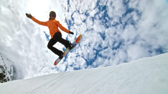 slo mo female snowboarder jumping in the half-pipe - snowboarding video stock e b–roll