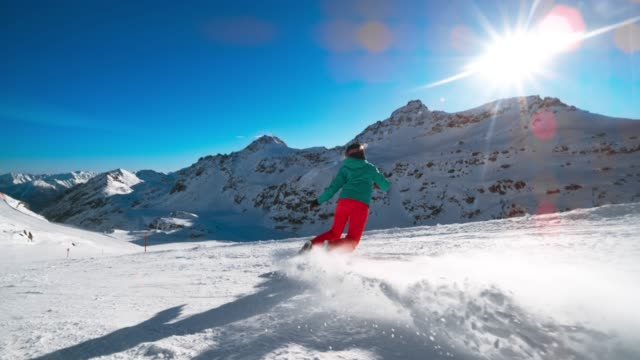 SLO MO TS Female snowboarder riding down the snow covered mountain slope in sunshine