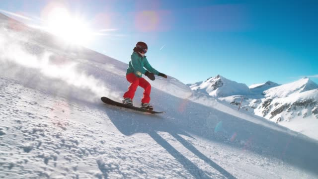 SLO MO TS Female snowboarder riding down the sunny mountain slope covered in fresh powder