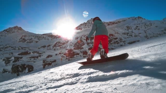 slo mo ts female snowboarder riding the sunny slope high in the mountains - sprzęt sportowy filmów i materiałów b-roll