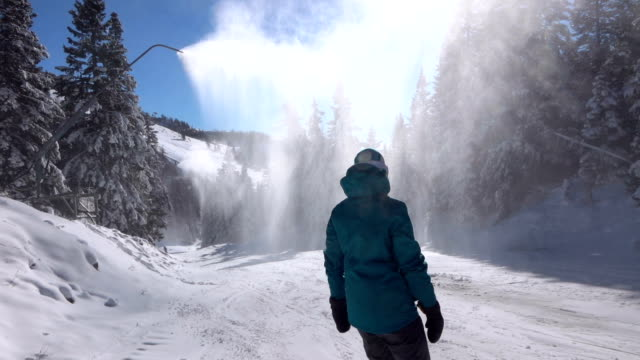 SLOW MOTION: Female snowboarding under the snow guns spraying artificial snow video