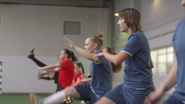 Female Soccer Athletes Doing Walking Front Leg Raises Side view shot of young professional female athletes performing walking front leg raises while training together on indoor soccer field pre game stock videos & royalty-free footage