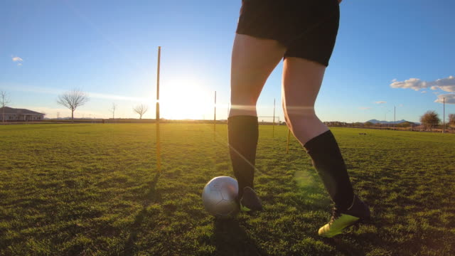 Female Soccer Player Doing Ball Drills A female high school soccer player in practice uniform practices her ball handling and dribbling skills while on the pitch in Arizona, USA. The young woman athlete works on her skills with drills at dusk with the sun shining through her silhouette. high school sports stock videos & royalty-free footage
