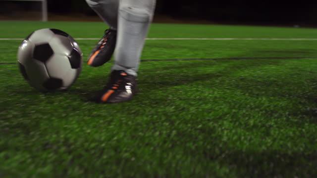 vidéos et rushes de une femme joueur de football dribbles dans le champ de nuit, tandis que ses adversaires glisser régler et défendre - football