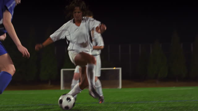A female soccer player dribbles down the field during a game at night A female soccer player dribbles down the field during a game at night kicking stock videos & royalty-free footage