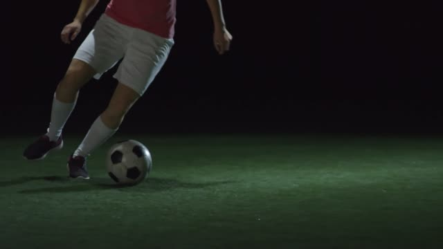 Female Soccer Player Dribbling Ball in Dark Arena video