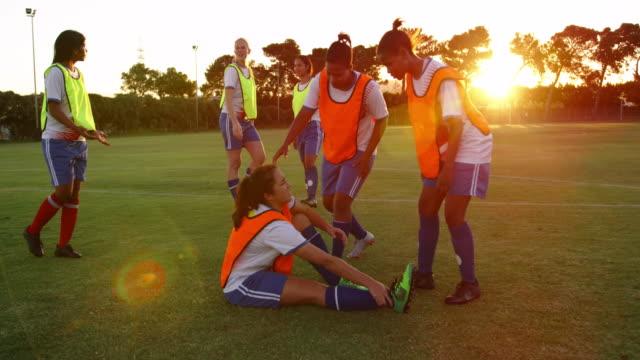kvinnlig fotbolls spelare hjälper lag kamrat att stå på fotbolls plan. 4k - skada bildbanksvideor och videomaterial från bakom kulisserna