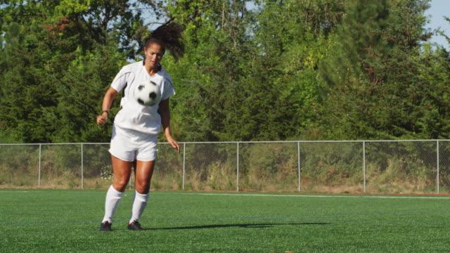 weibliche fußball-spieler erhält eine fußball und schuhe es auf dem feld - geköpft stock-videos und b-roll-filmmaterial