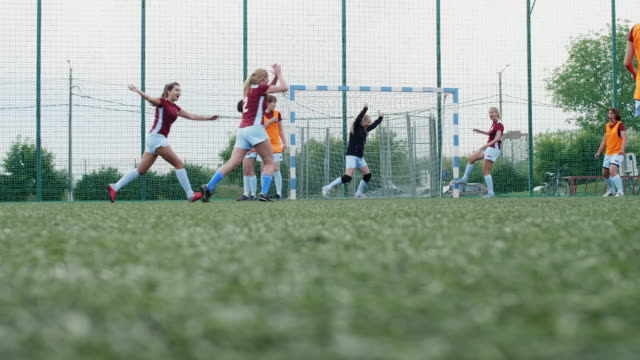 Female soccer player shooting goal in professional match Female soccer player shooting goal, celebrating it, handspringing and hugging her team while goalkeeper falling on grass and feeling sad in background goal post stock videos & royalty-free footage