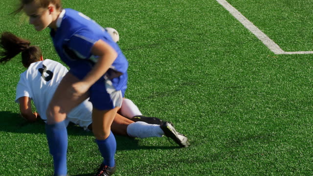 A female soccer player slide tackles an opponent during a game video