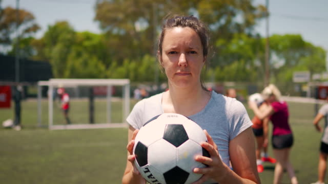 Female soccer player standing on soccer field and holding ball in his arm Portrait of mid adult women standing on soccer field and holding ball in her arms, while other teammates doing pregame routine pre game stock videos & royalty-free footage